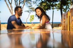 坐在酒吧桌ouside的愉快的夫妇在泰国 免版税库存照片