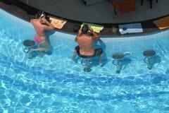 坐在酒吧的一个妇女和人由水池 库存图片