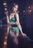 坐在酒吧的一件绿色礼服的典雅的女孩 免版税库存照片