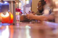 坐在酒吧的两个人种间人看他们的电话 库存照片