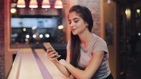 坐在酒吧的少妇使用她巧妙的电话在霓虹酒吧标志旁边 享受夜生活的妇女,当沟通时 股票录像