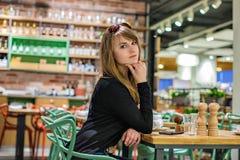 坐在酒吧的美丽的女孩 等待开胃酒的妇女 库存照片