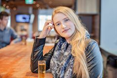 坐在酒吧的金发白肤金发的女孩喝酒精饮料 库存照片