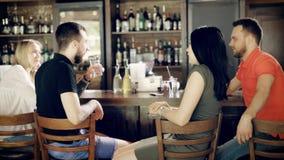 坐在酒吧逆饮用的饮料的两对年轻夫妇后面看法,当男服务员与窗口盒一起使用时 影视素材