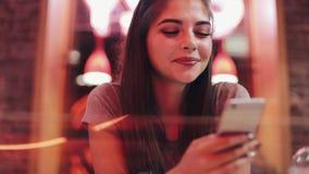 坐在酒吧,饮用的lemanade和使用她巧妙的电话的少妇在霓虹酒吧标志旁边 享受夜生活的妇女 股票视频
