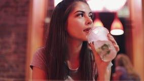 坐在酒吧,饮用的lemanade和使用她巧妙的电话的少妇在霓虹酒吧标志旁边 享受夜生活的妇女 股票录像