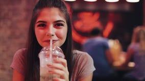 坐在酒吧,饮用的lemanade和调查照相机的年轻女人 享受夜生活的妇女,当沟通时 影视素材