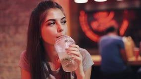 坐在酒吧,饮用的lemanade和调查照相机的年轻女人 享受夜生活的妇女,当沟通时 股票录像