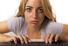 坐在重音的计算机书桌的年轻可爱的学生女孩或职业妇女与疲乏的蓝眼睛转动了带红色在长的h以后 免版税库存图片