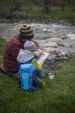 坐在野营的和观看的地图的火附近的少年 库存图片