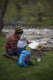 坐在野营的和观看的地图的火附近的少年 免版税库存图片