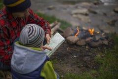 坐在野营的和观看的地图的火附近的少年 库存照片
