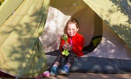 坐在野营的帐篷的小女婴在森林里 库存照片