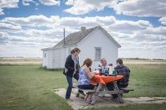 坐在野餐桌上的家庭吃午餐 免版税库存照片