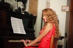 坐在钢琴的美丽的少妇在屋子里 库存照片