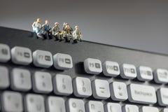 坐在键盘顶部的微型工作者 概念查出的技术白色 免版税库存照片