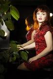 坐在镜子附近的一名美丽的红头发人妇女的画象 图库摄影
