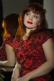 坐在镜子附近的一名美丽的红头发人妇女的画象 免版税库存照片
