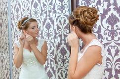坐在镜子附近的美丽的年轻新娘 免版税库存图片
