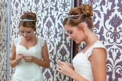 坐在镜子附近的美丽的年轻新娘 库存照片