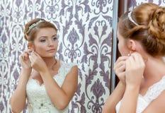 坐在镜子附近的美丽的年轻新娘 库存图片