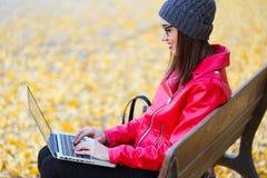 坐在长凳和使用她的膝上型计算机的美丽的少妇在秋天 图库摄影