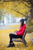 坐在长凳和使用她的膝上型计算机的美丽的少妇在秋天 库存照片