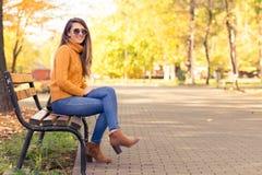 坐在长凳的俏丽的女孩在秋天公园 免版税库存照片