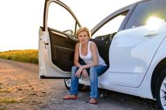 坐在门户开放主义的微笑的妇女她的汽车 库存照片