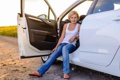 坐在门户开放主义的微笑的妇女她的汽车 免版税图库摄影