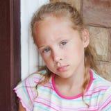 坐在门附近的哀伤的小女孩 免版税库存照片