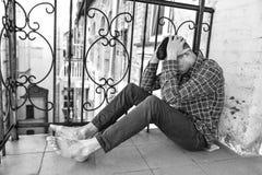 坐在阳台上的男性 人感觉可怕的感情痛苦和一蹶不振 上瘾者坏 库存图片