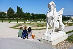 坐在雕塑下的一个小组年轻人 库存照片