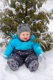 坐在雪的一个小男孩在树下在冬天 免版税库存图片