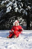 坐在雪的小女孩 免版税库存照片