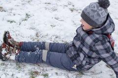 坐在雪的男孩 免版税库存图片