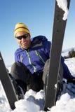 坐在雪的男性滑雪者在落以后 免版税库存图片