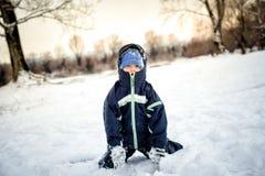 坐在雪的逗人喜爱的男孩 免版税库存图片