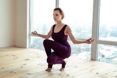 坐在非凡瑜伽姿势的平安的悦目年轻女人 库存照片