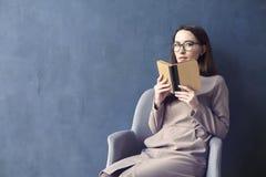 坐在顶楼办公室读书葡萄酒书的美丽的女实业家 被打开的书褐色盖子 深蓝墙壁背景,天光 库存图片