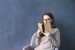 坐在顶楼办公室读书葡萄酒书的美丽的女实业家 调查被打开的书褐色盖子 深蓝墙壁背景 图库摄影