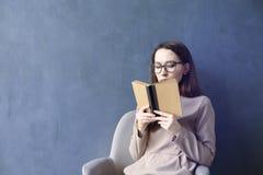 坐在顶楼办公室读书葡萄酒书的美丽的女实业家 调查被打开的书褐色盖子 深蓝墙壁背景 库存照片