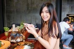 坐在顶楼咖啡馆的微笑的亚裔妇女画象  库存照片