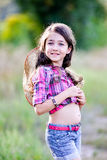 坐在领域的小女孩戴牛仔帽 库存图片