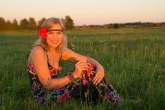 坐在领域的年轻美丽的妇女在日落 免版税库存照片