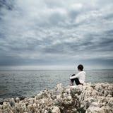 坐在风雨如磐的海的孤独的妇女 免版税库存图片