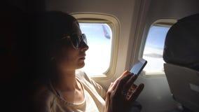 坐在飞机窗口附近在日落和使用手机的旅游妇女在飞行期间 图库摄影