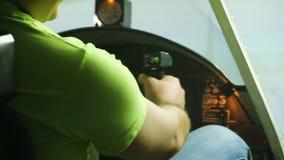 坐在飞机驾驶舱模拟器和显示好手标志的男性少年 影视素材