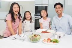 坐在餐桌上的一个微笑的家庭的画象在厨房里 免版税库存照片