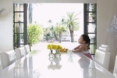 坐在餐桌上的体贴的女孩 免版税库存照片